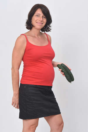 pregnant woman holding sausage on white background