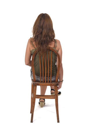 rear view of a woman in denim skirt sitting on a chair on white background