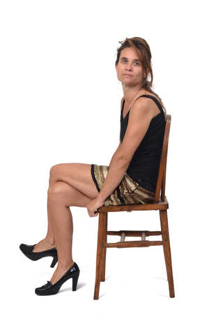 side view of a woman in skirt sitting on a chair on white background, looking at camera and serious and legs crossed