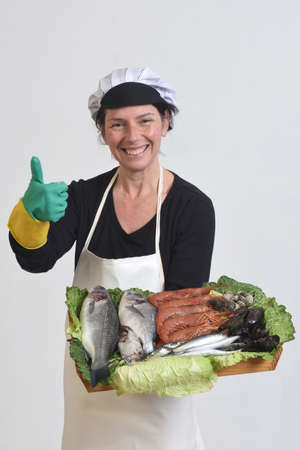 fishmonger showing a plate with fish and seafood and making a thumb up sign on white background.
