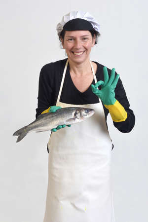 portrait of a fishmonger holding and ok sign at a sea bass on white background Banque d'images