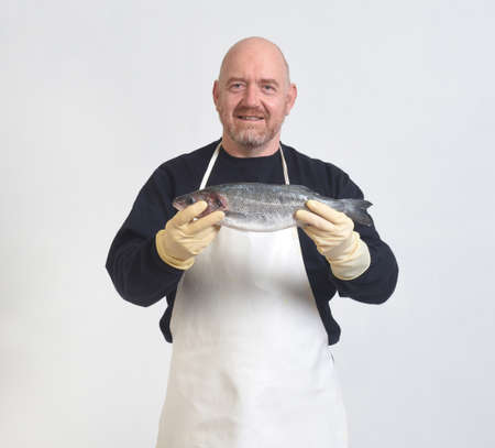 portrait of a fishmonger holding a sea bass on white background