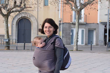 portrait of a woman carrying her child in an urban setting Zdjęcie Seryjne