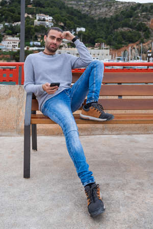Man sitting on a bench holding a mobile phone, looking straight ahead. With one leg stretched out and the other on top of the bench. Wearing a watch, gray jumper and jeans. Alicante, javea Foto de archivo