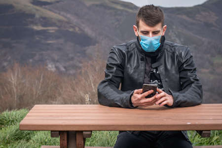 Young handsome man with facial mask texting on his phone sitting alone on a picnic table