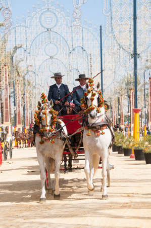 JEREZ DE LA FRONTERA, SPAIN-MAY 8: People on draft horses walking in the royal house of the fair at the Horse Fair on May 8, 2018 in Jerez de la Frontera