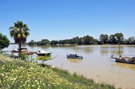 Boats on the Guadalquivir River as it passes through Coria del Rio, province of Seville, Spain