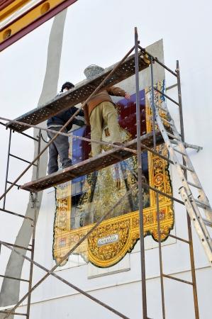 retablo: Dos alba�iles colocando un retablo religioso azulejo Foto de archivo