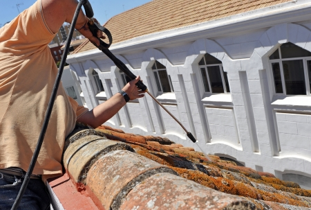 Construction worker cleaning the tiles on a roof Standard-Bild