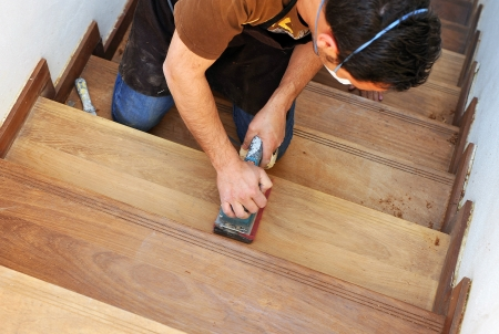 sanding: Carpenter sanding the steps of a staircase Stock Photo