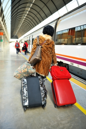 Woman with bags in the train station in Seville, Spain