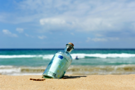 Hundred euros in the bottle on the beach photo