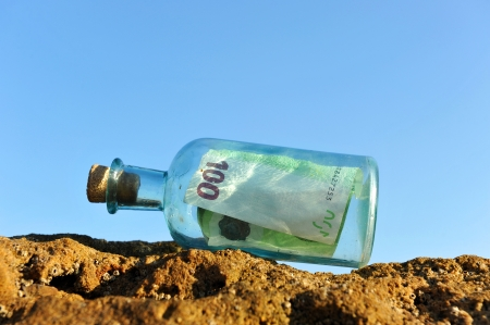 Hundred euros in the bottle on the rock photo