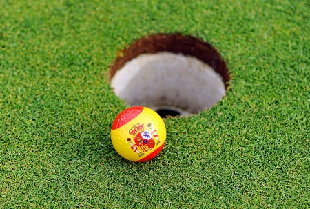 Golf ball edge of the hole, flag of Spain Stock Photo