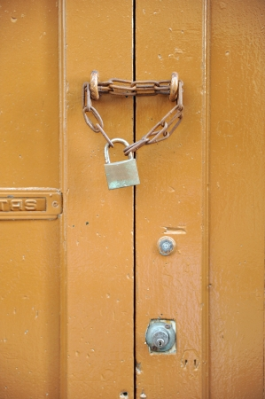 Closed wooden door with lock and chain photo
