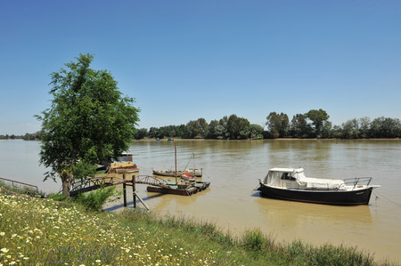 Boats on the Guadalquivir river passing by Coria del Rio, Province of Sevilla, Andalusia, Spain