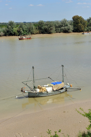 Boat in the river Guadalquivir passing by Coria del Rio, Province of Sevilla, Andalusia, Spain Banco de Imagens