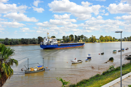 Cargo boat on the Guadalquivir river passing by Coria del Rio, Province of Sevilla, Andalusia, Spain