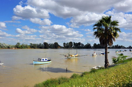 Boats in the river Guadalquivir passing by Coria del Rio, Province of Sevilla, Andalusia, Spain