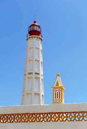 Maritime lighthouse and chimney, Culatra Island, region of Algarve, southern Portugal, Europe photo