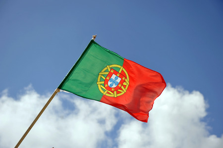 Portuguese flag in the wind with blue sky with clouds photo