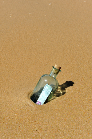 100 euro banknote in a bottle found on the sand photo