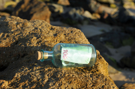 100 euro bills in a bottle found on the beach rocks photo