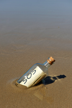 Distress Message in a bottle found on the beach sand photo