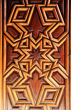 Old wooden door decorated with arabesques of stars, church of Santa Ana, Seville, Andalusia, Spain photo