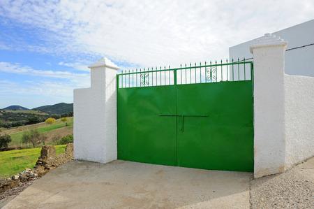 puerta de metal: Gran puerta de metal verde, entrada a una granja en el campo, Andaluc�a, Espa�a Foto de archivo