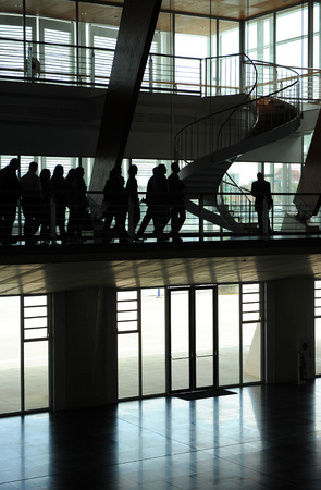 Group of business people at a convention center, silhouettes photo