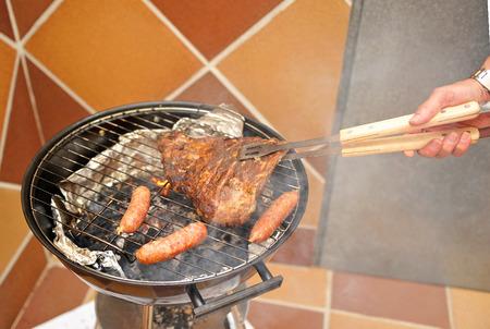 chorizos asados: Cocinar una barbacoa para los amigos en el patio trasero Foto de archivo