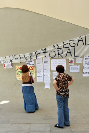 Two women in front of a wall with manifestos and banners, popular expression claims people