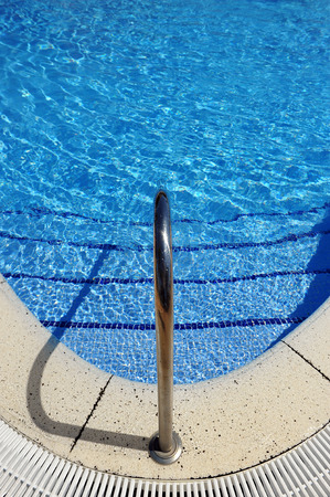 Stainless steel ladder near clear blue water of swimming pool