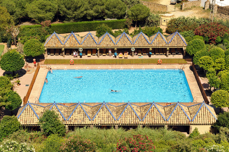 Swimming pool, tourists sunbathing on the loungers, Carmona, Andalusia, Spain