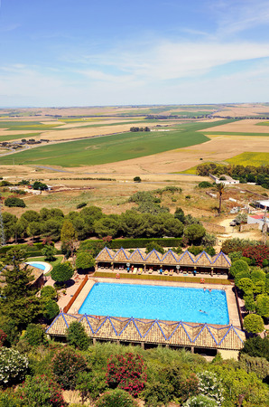 Tourists sunbathing on the loungers at poolside in the countryside, Carmona, Andalusia, Spain