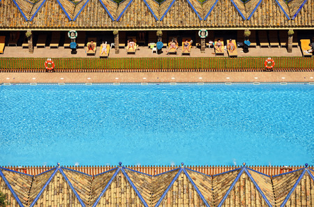loungers: Tourists sunbathing on the loungers at poolside, Carmona, Andalusia, Spain Editorial