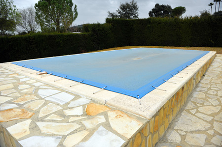 winter day: Swimming pool with a tarp for protection in winter