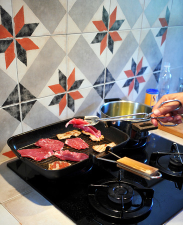 Grilled sirloin, steaks cooking on a gas cooker, pots and pans in the kitchen photo