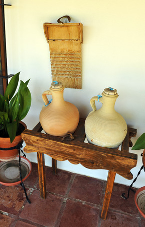 washboard: Large ceramic jugs for fresh water, washboard, house in town Stock Photo