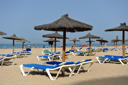 loungers: Sun loungers and parasols, Victoria Beach, Costa de la Luz, Cadiz, Andalusia, Spain Stock Photo