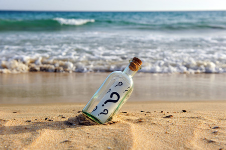 Bottle with message on the sand beach, question marks, questions, ask questions