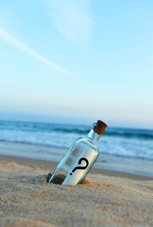 Message in a bottle on the sand beach, question mark, question, doubt Banco de Imagens