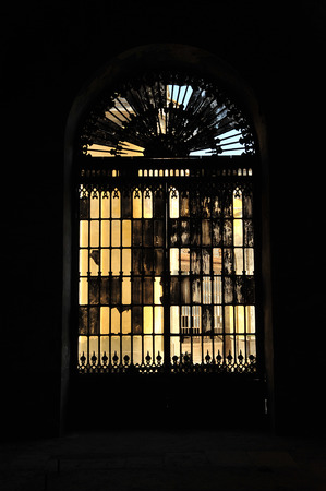and diurnal: Large iron door with broken glass in an old building, Seville, Spain