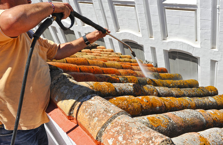 Worker cleaning a roof with high pressure water Stock Photo
