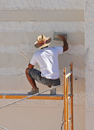repeal: A bricklayer working on the construction of a house