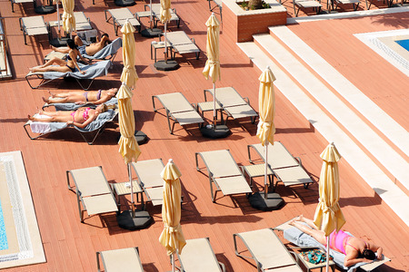 sun bathers: Terrace with loungers and parasols in the hotel swimming pool