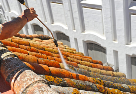 Worker cleaning shingles on a roof throwing water at high pressure