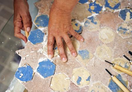 restoring: Woman restoring an ancient pavement stars