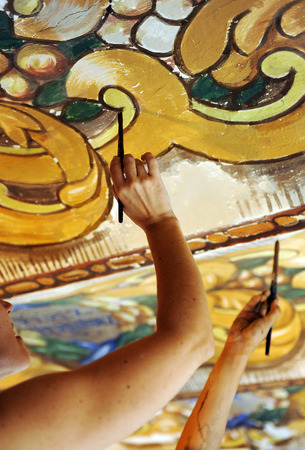 restoring: Two women restoring some ancient mural paintings on the ceiling